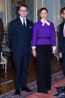 Damit der Business-Look nicht allzu hart wirkt, kombiniert Prinzessin Victoria ihren lilafarbenen Blazer mit einer weißen Seidenbluse, die sie am Kragen zu einer geschwungenen Schleife gebunden hat.