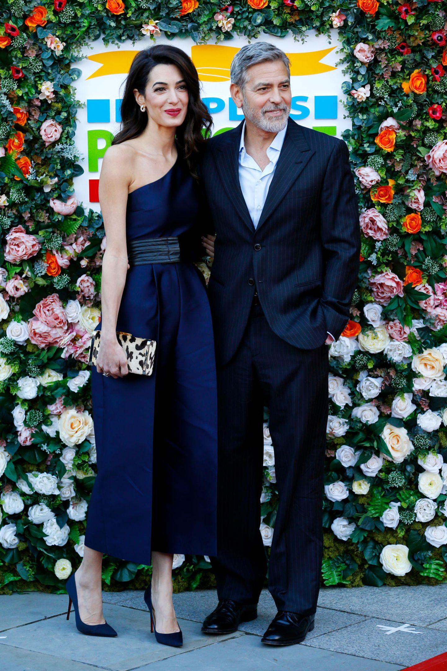 Bei einer Galaam 14. März 2019 in Edinburgh zeigt sich Amal Clooney in einem eleganten One-Shoulder-Jumpsuit von Stella McCartney aus Satin. Ein schwarzer Taillengürtel betont zusätzlich die schlanke Silhouetteder 41-Jährigen – dunkelblauePumps lassen den Look außerdem glamourös wirken.