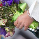 An ihrer linken Hand funkelte neben demgoldfarbenen Ehering ein mit Diamanten besetztes Armband.
