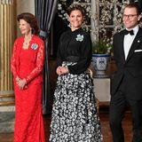 """Beim Dinner für das schwedische Parlament macht sich Prinzessin Victoria besonders """"gastgeber-fein"""". Zu einer schwarzen Bluse kombiniert sie einen Rock, der durch seine florale 3D-Optik und die Farbkontraste besonders ins Auge sticht."""