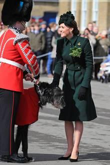 """Catherines Kopfbedeckung ist farblich auf ihren Mantel abgestimmt. Ihre Handschuhe und Pumps setzen in schwarz einen stylischen Akzent. Ihre """"Shamrock""""-Brosche (Shamrock ist dasinoffizielle Nationalsymbol Irlands, ein dreiblättriges Kleeblatt) ist eine Sonderanfertigung von Cartier."""