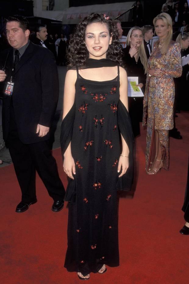 """1999  Mit ihren 16 Jahren ist Mila Kunis bereits ein großer Serien-Star. Bekannt wird sie durch """"Die wilden Siebziger"""". Ihr Stil ist dementsprechend noch nicht ganz """"ausgereift"""". Auf der Suche nach ihrem eigenen Style schlüpft sie in unterschiedliche Looks und probiert sich aus. So auch hier mit einem langen schwarzen Kleid mit floralen Details."""
