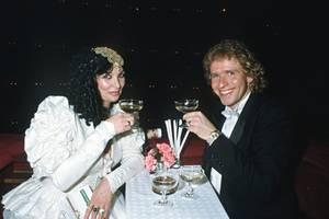 Für ihren Besuch beim Wiener Opernball im Jahr 1986 werfen sich die Gottschalks in Schale. Während Thea auf ein weißes Kleid mit aufwendig gerüschten Ärmeln und goldenem Kopfschmuck setzt, trägt Thomas einen schwarzen Smoking mit weißer Fliege.