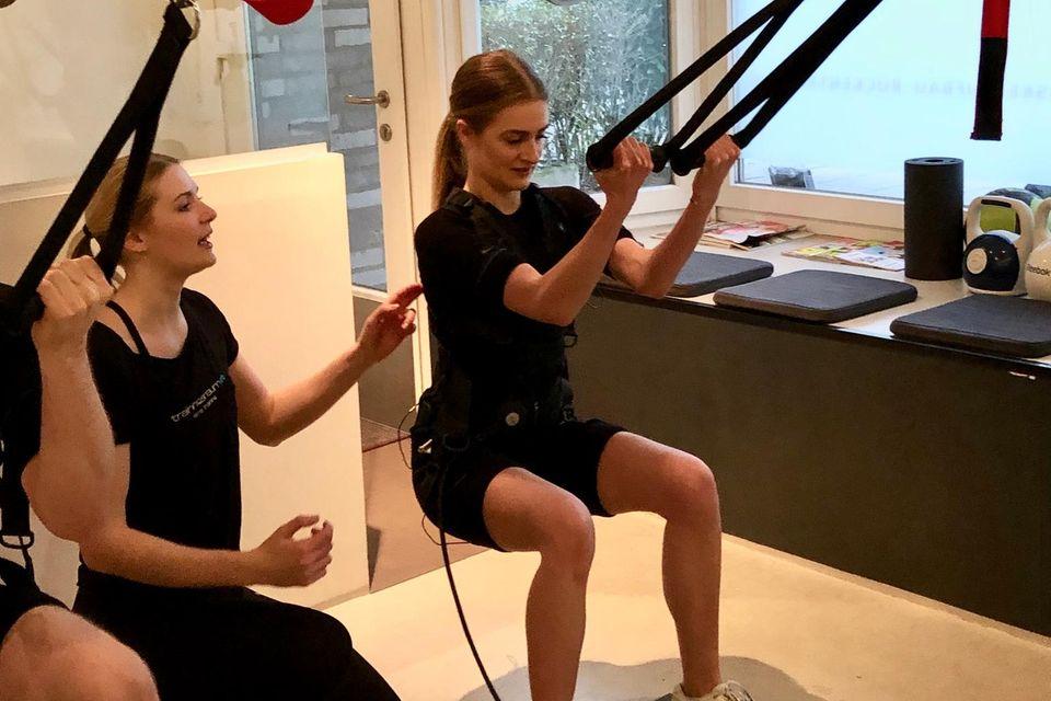Während des Workouts wird Tabea von einer Trainerin angeleitet. Zu dem Sportprogramm gehören unter anderem auch Squats an den TRX-Bändern.