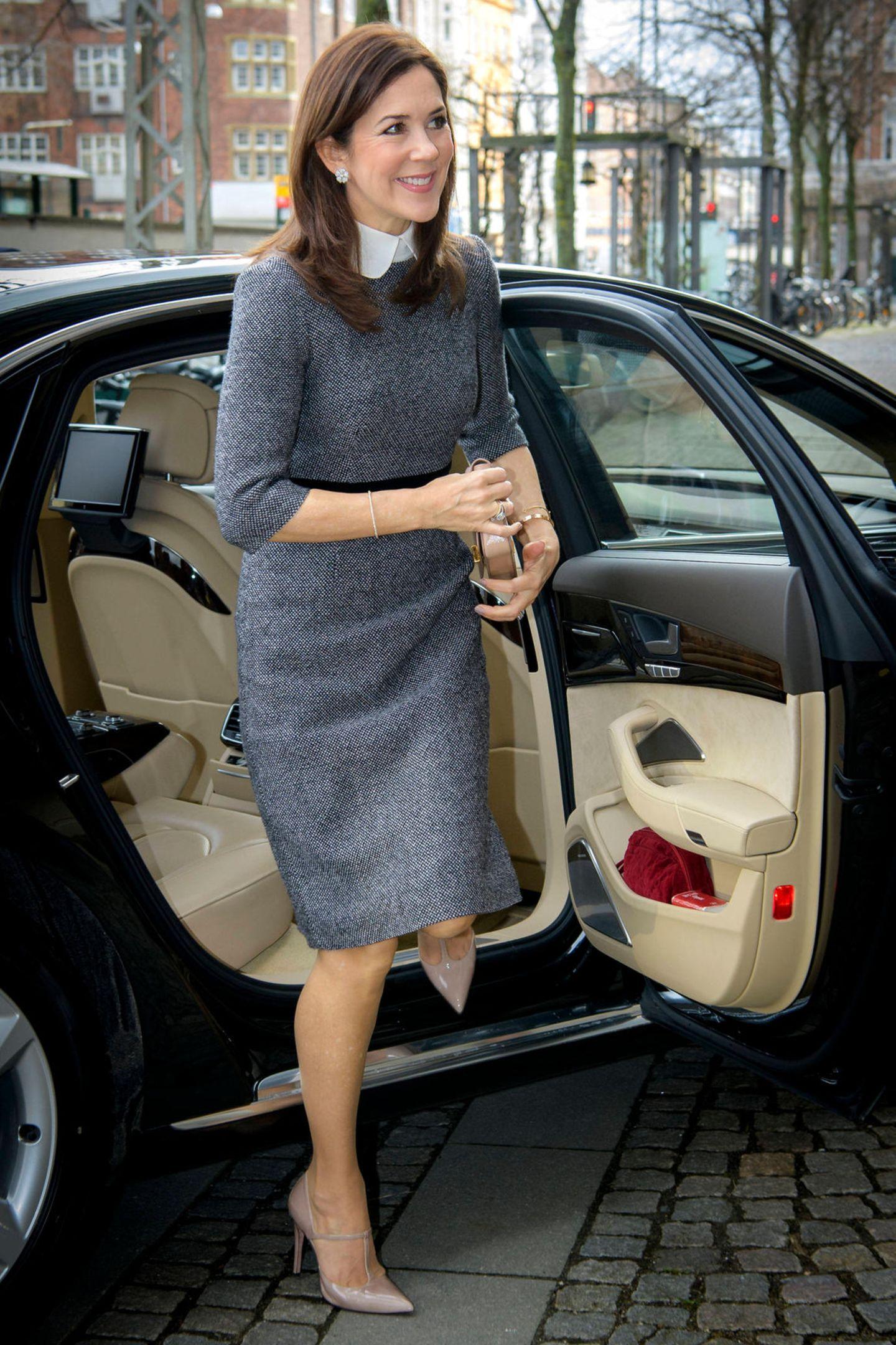 Prinzessin Mary ist für ihre Stilsicherheit bekannt. Bei ihrem Besuch der Universität von Kopenhagen begeistert sie in einem grauen Kleid von Prada zu dem sie beige Lackpumps und eine passende Clutch kombiniert.