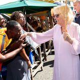 Herzogin Camilla bekommt von einem jungen Mann einen Handkuss.