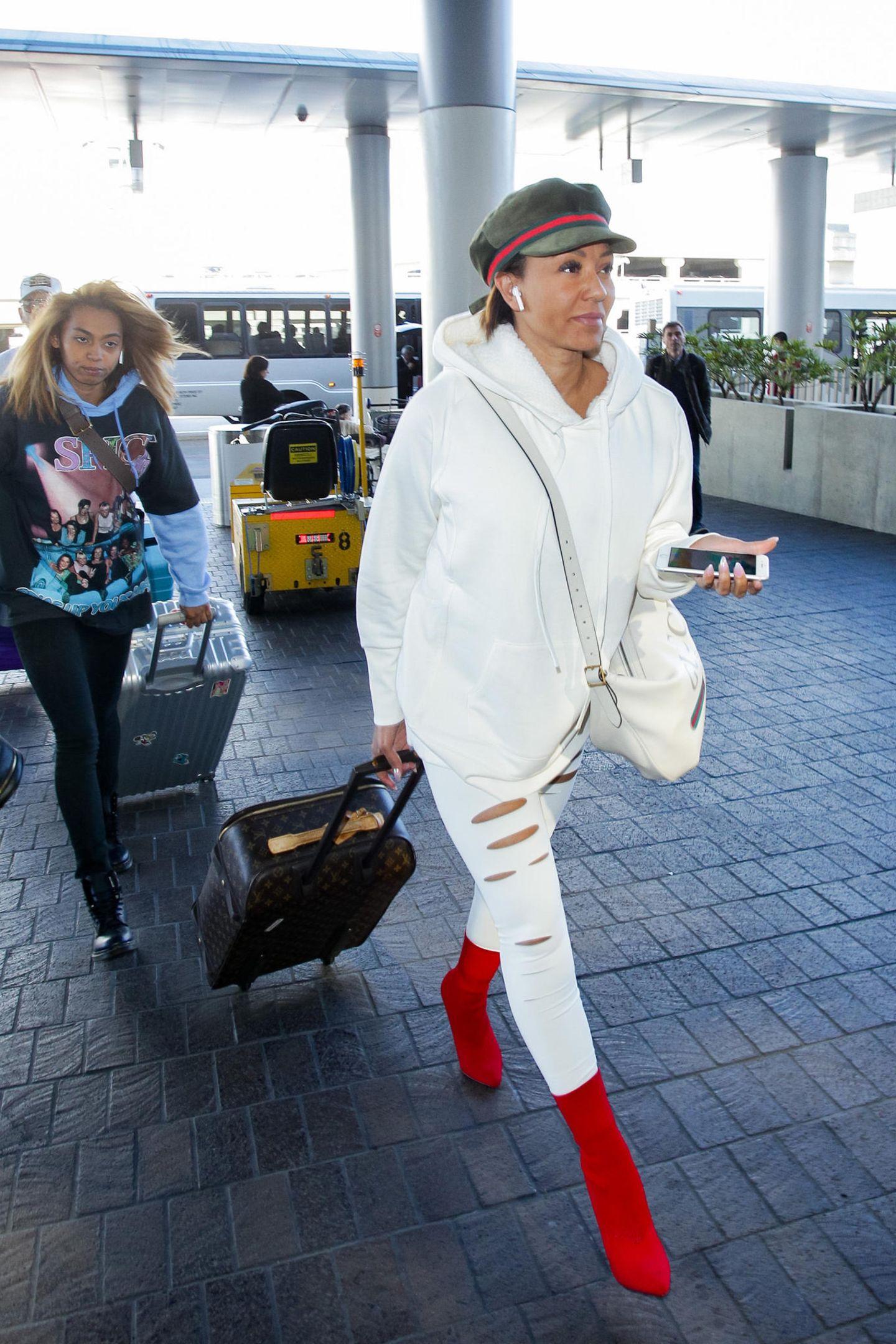 Mit einem weißenHoodie undeiner zerrissenen Leggings geht Mel B. auf Reisen. Den weißen Style kombiniert sie mit knallroten Stiefeletten und einer Schiebermütze. Paparazzi erwischen das ehemalige Spice Girl am Flughafen von Los Angeles, wo sie schnell einen Louis-Vuitton-Koffer hinter sich herzieht. Doch damit nicht genug Stauraum: Eine Gucci Bag hat die 43-Jährige für ihren Flug auch noch dabei.