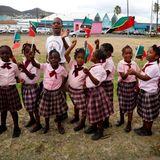 Schulkinder warten Fähnchen schwenkend auf die Ankunft des britischen Prinzenpaars.