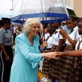 Hände schütteln bei Schlechtwetter: Camilla lässt sich trotz Regen die Laune nicht verderben und begrüßt bei ihrer Ankunft im Inselstaat St. Kitts und Nevis die wartenden Fans.