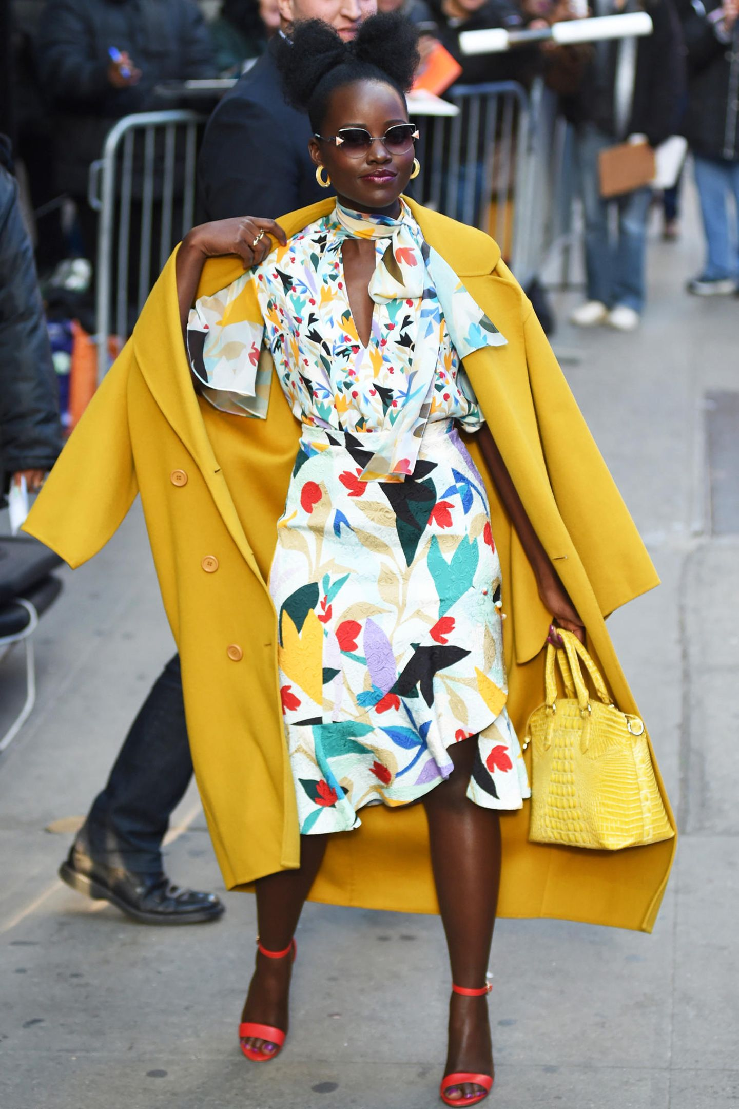"""Hier kommt der Frühling! Lupita Nyong'o zeigt sich vor dem """"Good Morning America""""-Studioam New Yorker Times Square in einem floralen Look von Prabal Gurung, den sie mit einem sonnig gelben Mantel kombiniert."""