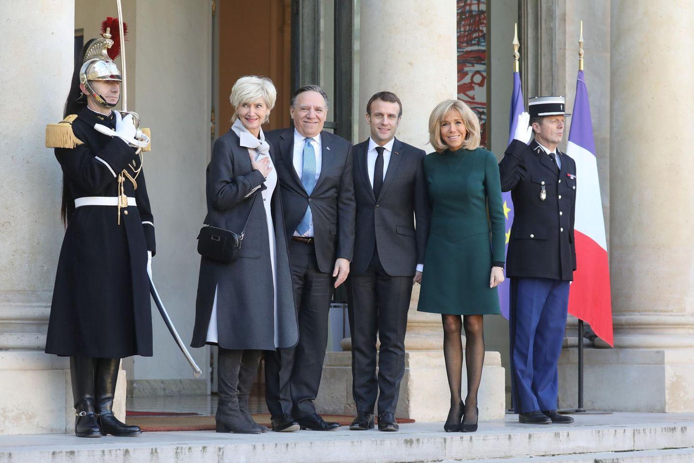 Zurück in Paris trägt Brigitte Macron ein dunkelgrünes Kleid, das knapp über dem Knie endet. Dazu trägt sie eine schwarze Strumpfhose und schwarze Pumps.