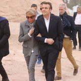 Auf dem Weg in einen Tempel im Süden Ägyptens klammert sich Frankreichs First Lady an ihren Ehemann, Emmanuel Macron. Sie trägt einen grauen Anzug mit Reißverschluss und farblich passende Sneaker.