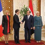 Während des Staatsbesuch in Ägypten zeigt sich Premiere Dame Brigitte Macron in Knallrot. Über ihrem knielangen Etui-Kleid trägt sie einen schwarzen Mantel. Dazu kombiniert sie schwarze Pumps.