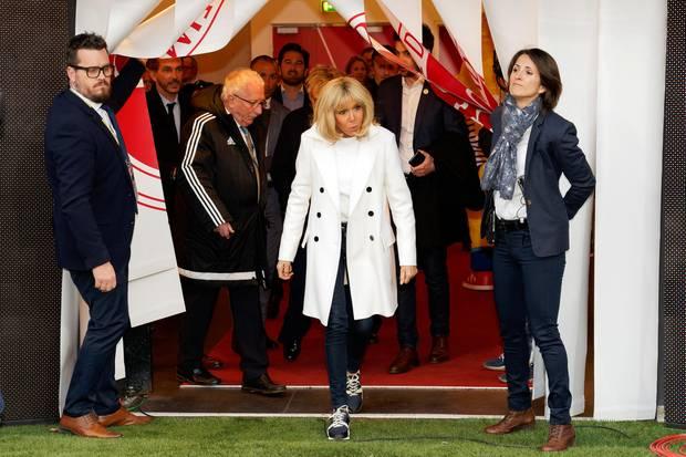 Für ein Charity Match im französischen Reims zeigt Brigitte Macron, dass auch ein sportlicher Look elegant aussehen kann. Zu einem weißen Trenchcoat mit schwarzen Knöpfen kombiniert sie eine schwarze Jeans und coole Sneaker von Louis Vuitton, die für stolze 650 Euro erhältlich sind.