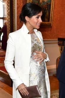 Schützend legt dieFrau von Prinz Harry die Hand auf ihren Bauch – eine Geste, die wir bereits mehrfach bei ihr gesehen haben.