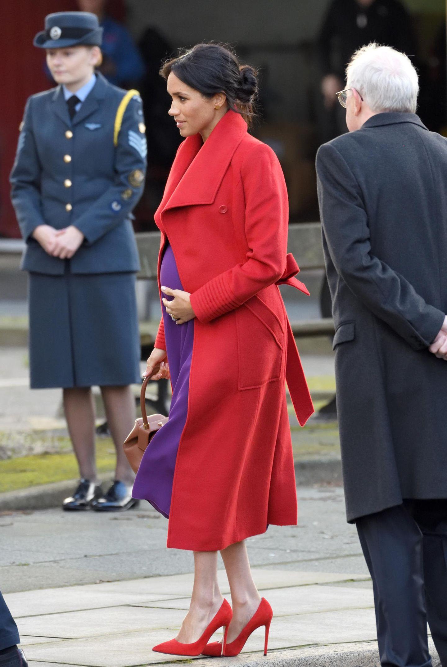 In einem violetten Kleid von Babaton für Aritzia und einem ebenfalls roten Mantel mit Gürtel zieht sie mit diesem Look alle Blicke auf sich und ihre Babykugel.