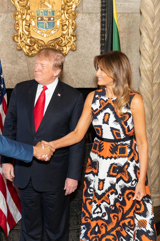 """Melania Trump schüttelt in einem Midi-Kleid mitauffälligem Print dem jamaikanischenPolitikerAndrew Holness die Hand. Was keiner weiß: Die Kreation des britischen Labels """"L.K. Bennett"""" ist derzeit im Sale und kostet umgerechnet nur etwa 250 Euro. Für Melanias Verhältnisse ein echtes Schnäppchen ..."""
