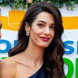 Amal Clooney legt in einer dunkelblauen a-symmetrischen Robe auf sehr glamouröse Art und Weise ihre Schulterpartie frei. Besonders schön: Die zurückgelegten Haare und der dezente Ohrring richten ebenfalls den Fokusauf Amals Schlüsselbein.