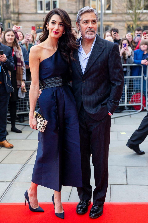 Das dunkelblaue Kleid der Ehefrau von George Clooney zaubert durch den integrierten Taillengürtel eine wunderbare Silhouette. Abgerundet wird ihr Look durch eine Clutch mit Leo-Print und zum Kleid farblich abgestimmte Pumps.