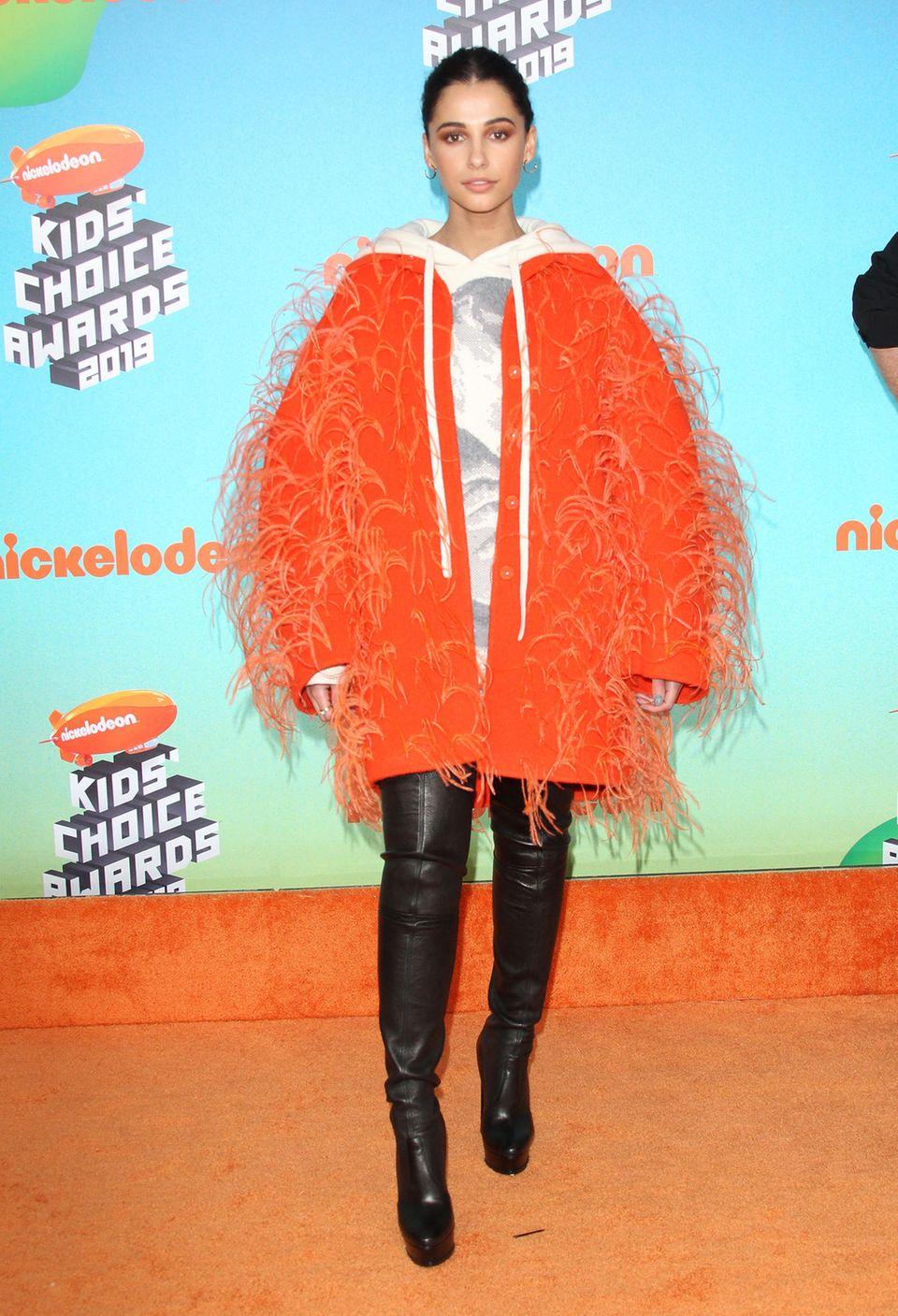 Upps, was soll denn dieser Zottel-Mantel in XXL und in der Knallfarbe Orange, liebe Naomi Scott? Der Mantel wirkt an der britischen Schauspielerin und Sängerin Naomi Scott nicht nur unförmig, auch fragt man sich, ob sie gerade von einer Bad-Taste-Party gekommen ist.