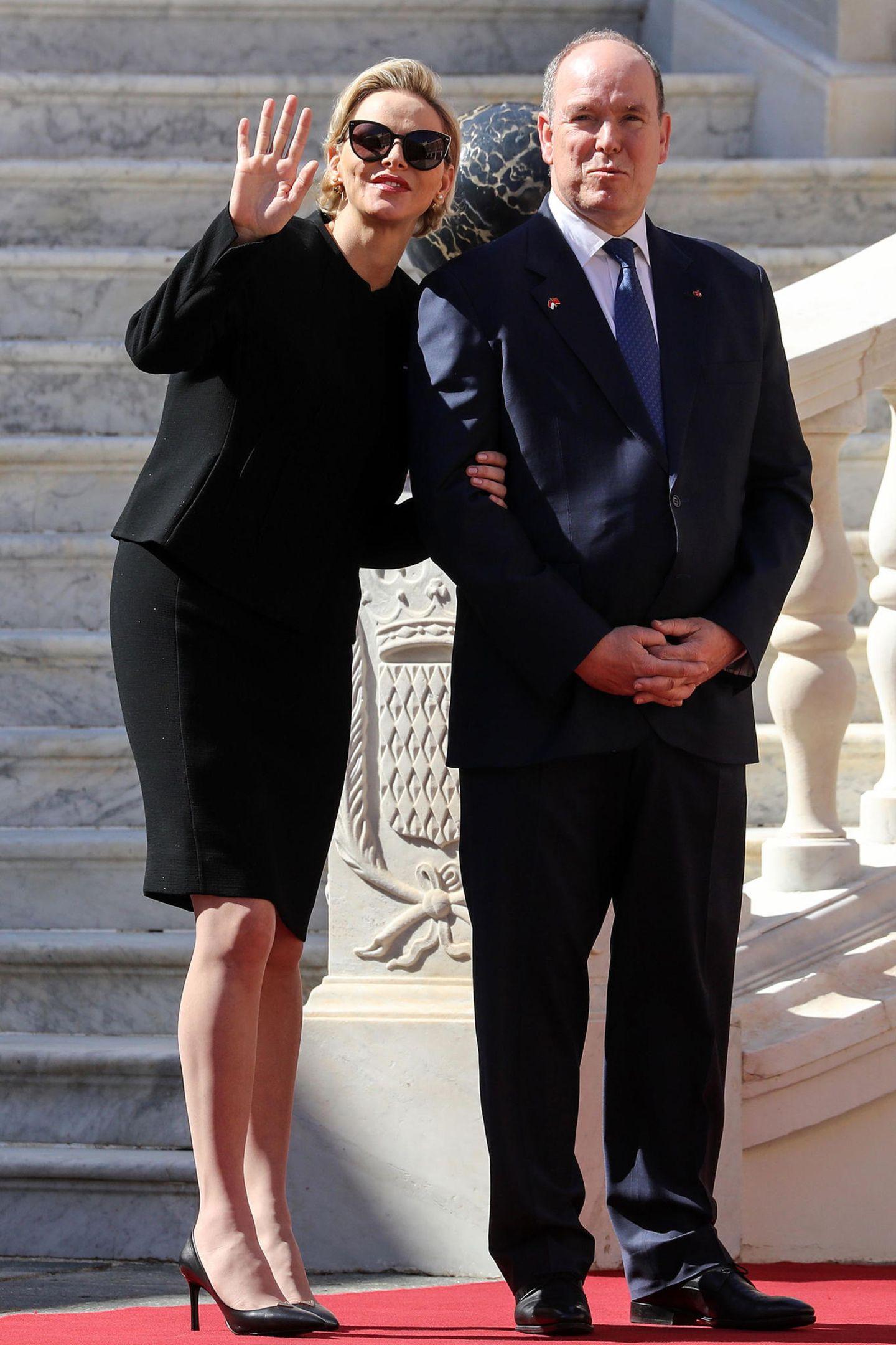 Ihre Stimmung vor dem Palast ist allerdings nicht ganz so düster wie ihr Beerdigungslook. Fröhlich winkt sie jemandem zu.
