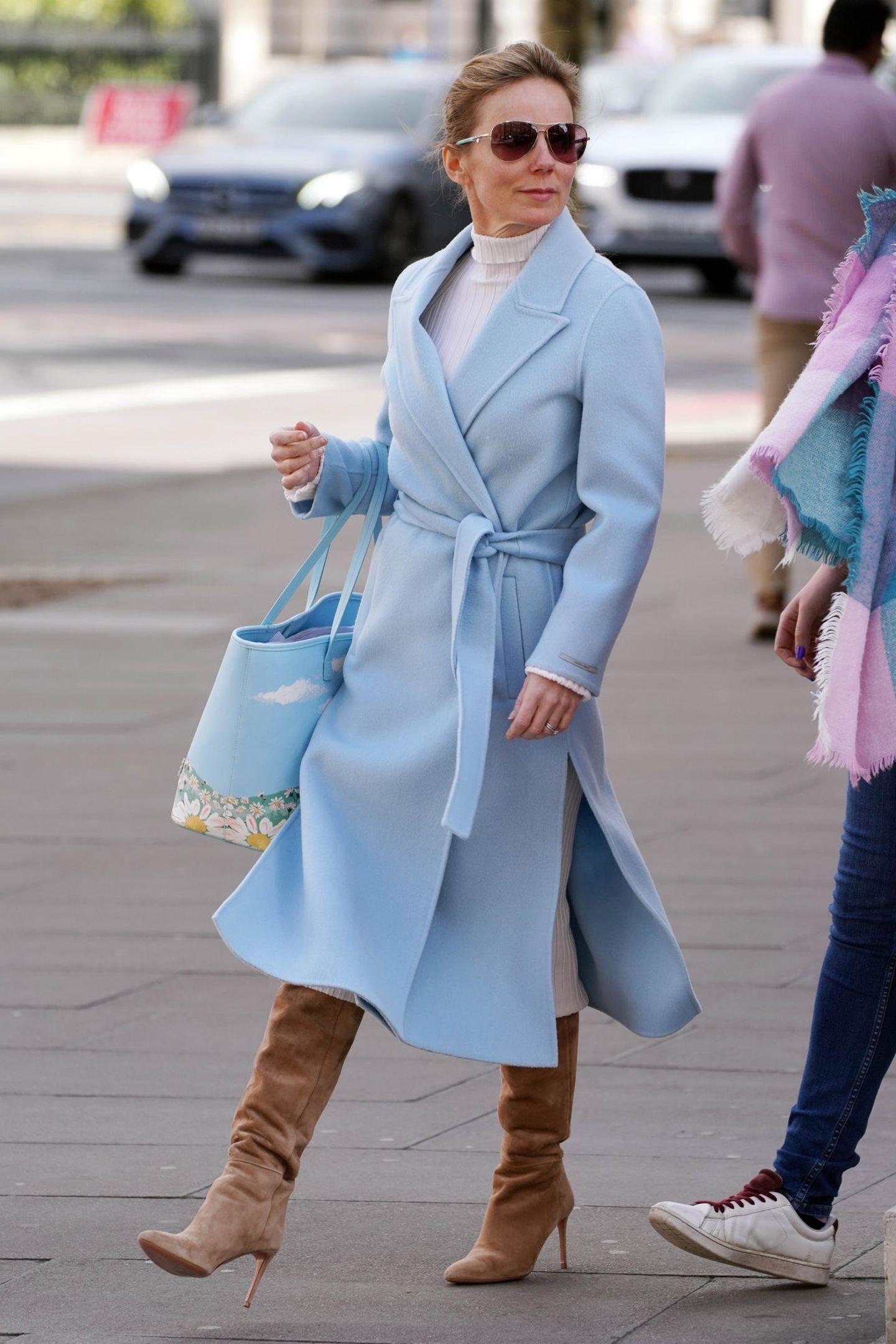 """Zum babyblauen Luxusmantel von Max Mara kombiniert """"Spice Girls""""-Star Geri Horner hohe Wildleder-Stiefel und einen Shopper aus der Disney-Kollektion von Designer Christopher Kane."""