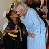 Camilla bekommt ein Küsschen von einem kleinen Mädchen, das sich als Biene verkleidet hat.