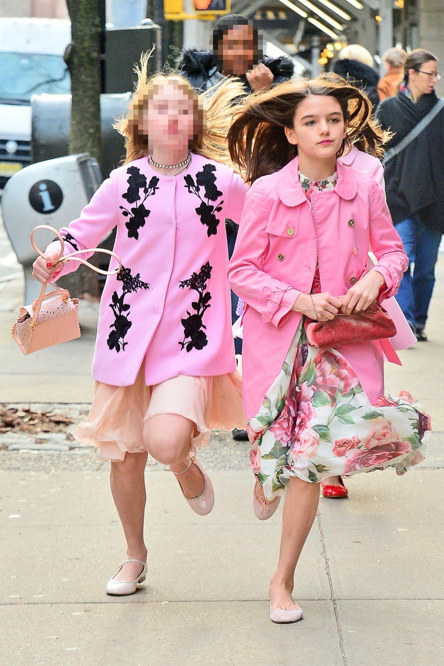 Suri Cruise spielt wie ein ganz normales Mädchen auf den Straßen New Yorks, weil sie jedoch kein ganz normales Mädchen ist, sind die Paparazzi ihr stets auf den Fersen. In ihrem geblümten Kleid und einer pinken Jacke ist Suri nicht gerade unauffällig.