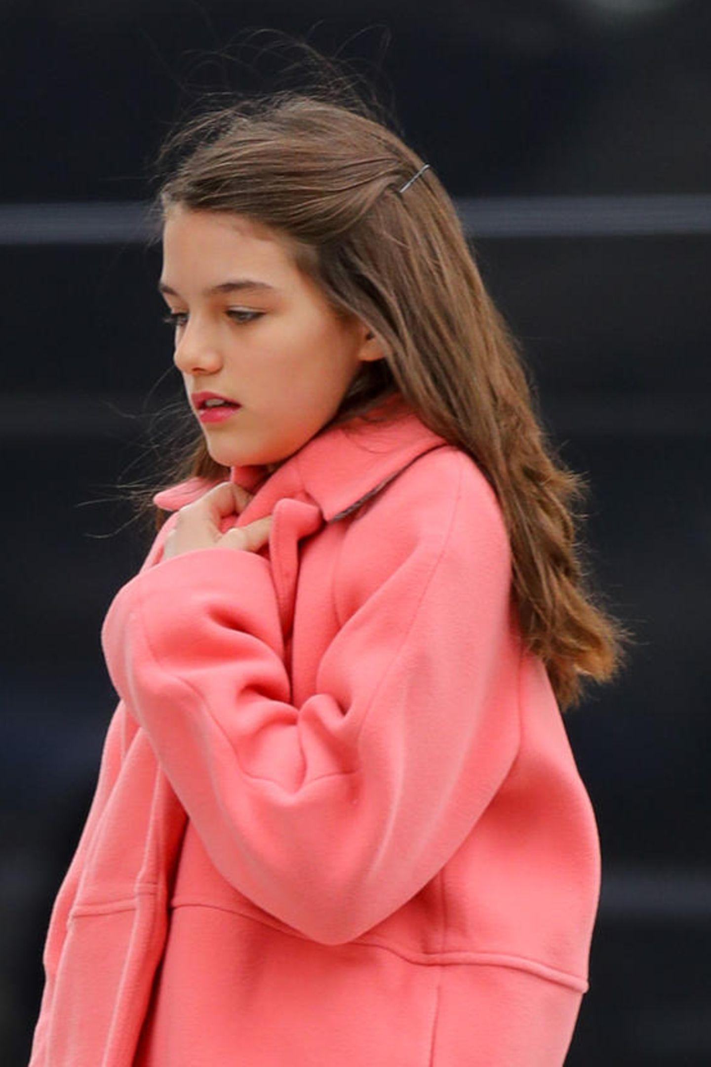 Ihr brünettes Haar trägt sie offen und auf den Lippen trägt sie einen farblich passenden Lippenstift. Ganz schön groß, die Kleine!