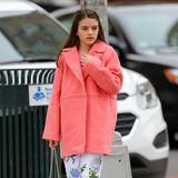 Suri Cruise schlendert in einem coral-farbenen Mantel durch die Straßen New Yorks. Dazu trägt sie eine geblümte Culotte und pinke Puma-Sneaker. In der Hand hält sie lässig eine beige Handtasche.