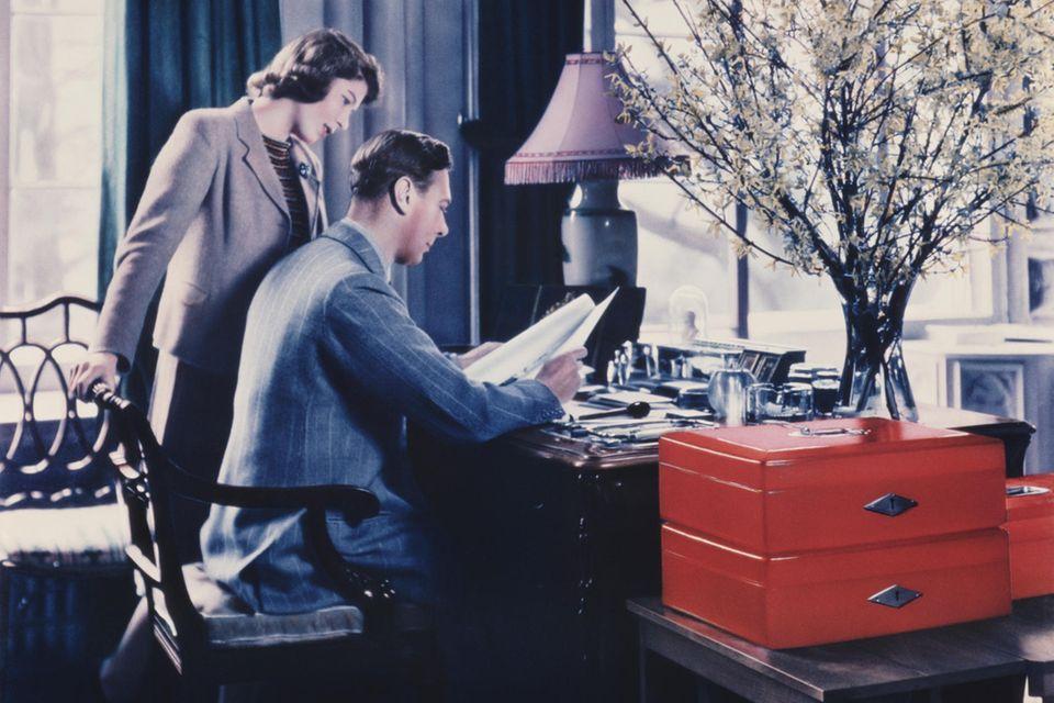 Prinzessin Elizabeth, die spätere Queen, schaut ihrem Vater, König George VI.,in seinem Arbeitszimmer in Windsor Castle über die Schulter. Die roten Boxen sind, natürlich, dabei. Die Aufnahme stammt vom 11. April 1942.
