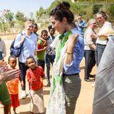 """""""Oder soll ich lieber dieses Kleid tragen?"""", scheint Prinzessin Mary die anwesenden Kinder im Flüchtlingscamp zu fragen. Die traditionelle Tracht in Weiß und Grün hätte ihr sicherlich gut gestanden."""