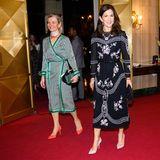 An der Seite vonEntwicklungsministerinUlla Tørnæsstrahlt Kronprinzessin Mary in einem eleganten, schwarzen Abendkleid. Das zarte Rosa der Musterung greift die gebürtige Australierin gekonnt in ihrer Schuhwahl auf.