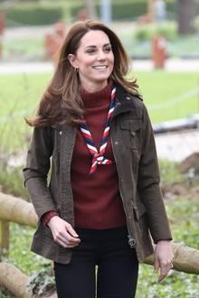 """So bodenständig gekleidet, haben wir Herzogin Catherine lange nicht mehr gesehen. Für ihren Besuch der Organisation """"UK Scouting"""" in Essex wählt die 37-Jährige einen warmen weinroten Rollkragenpullover des Labels J.Crew, den sie mit einem gestreiften Tuch kombiniert."""