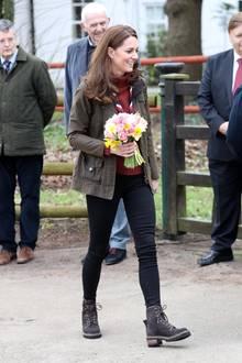 """Ihre schmalen Beine hüllt Herzogin Kate in schwarze Skinny-Jeans von Zara und stapft in Boots von Chloe über das Gelände. Auch ihre Jacke von Barbour passt perfekt zu ihrem """"Wander-Look""""."""