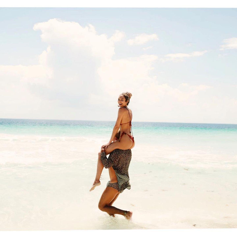 Candice Swanepoel lässt sich durchs Wasser tragen und präsentiert dabei ihre beneidenswerte Figur. Die starken Schultern gehören aber nichtihrem Ehemann, sondern dem besten Freund des Models. Eduardo Bravin ist Fotograf und für seine flippige Art bekannt. Gemeinsam haben sie sichtlich Spaß!