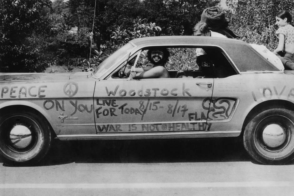 Woodstock50 steht im Jahr 2019 an. Damals waren das Publikum der Star von Woodstock. Abgebildet ist ein Musikfan auf dem Festival, der sein Auto in Anti-Kriegsslogans für Liebe und Frieden bemalte.