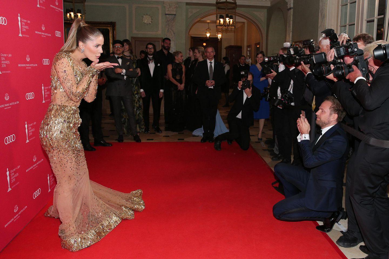 Victoria Swarovski, bezaubernd im Gold-Look von AlinLe' Kal, wirft zarte Küsse in die Kameras.