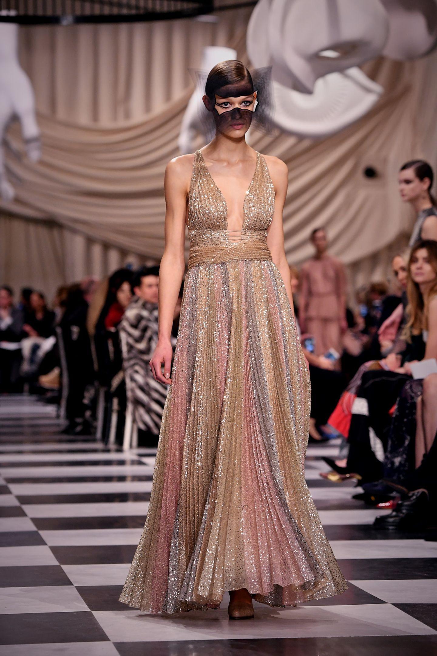 Das Kleid von Beatrice stammt aus der Haute-Couture-Kollektion von Dior und wurde im Januar 2018 während der Pariser Modewoche auf dem Laufsteg gezeigt. Der tiefe Ausschnitt und eindunklerMundschleier lassen den Look sexy wirken.