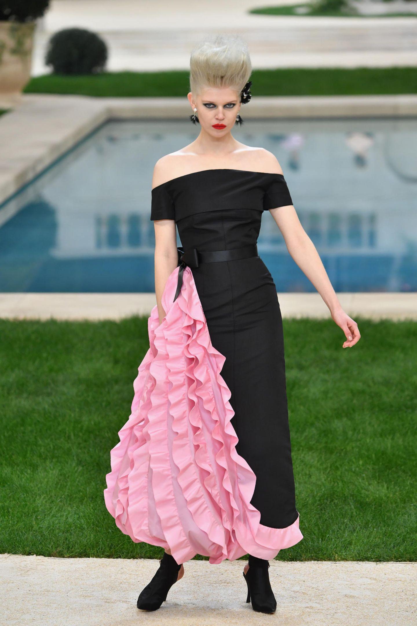 Auch der Chanel-Look, den Prinzessin Caroline für den Rosenball wählte, wirkt auf dem Laufsteg ganz anders: Während der Pariser Fashion Week im Januar 2019 präsentiert ein Model mit kurzen, abstehenden Haaren das schwarze Kleid mit rosa Rüschendetails.