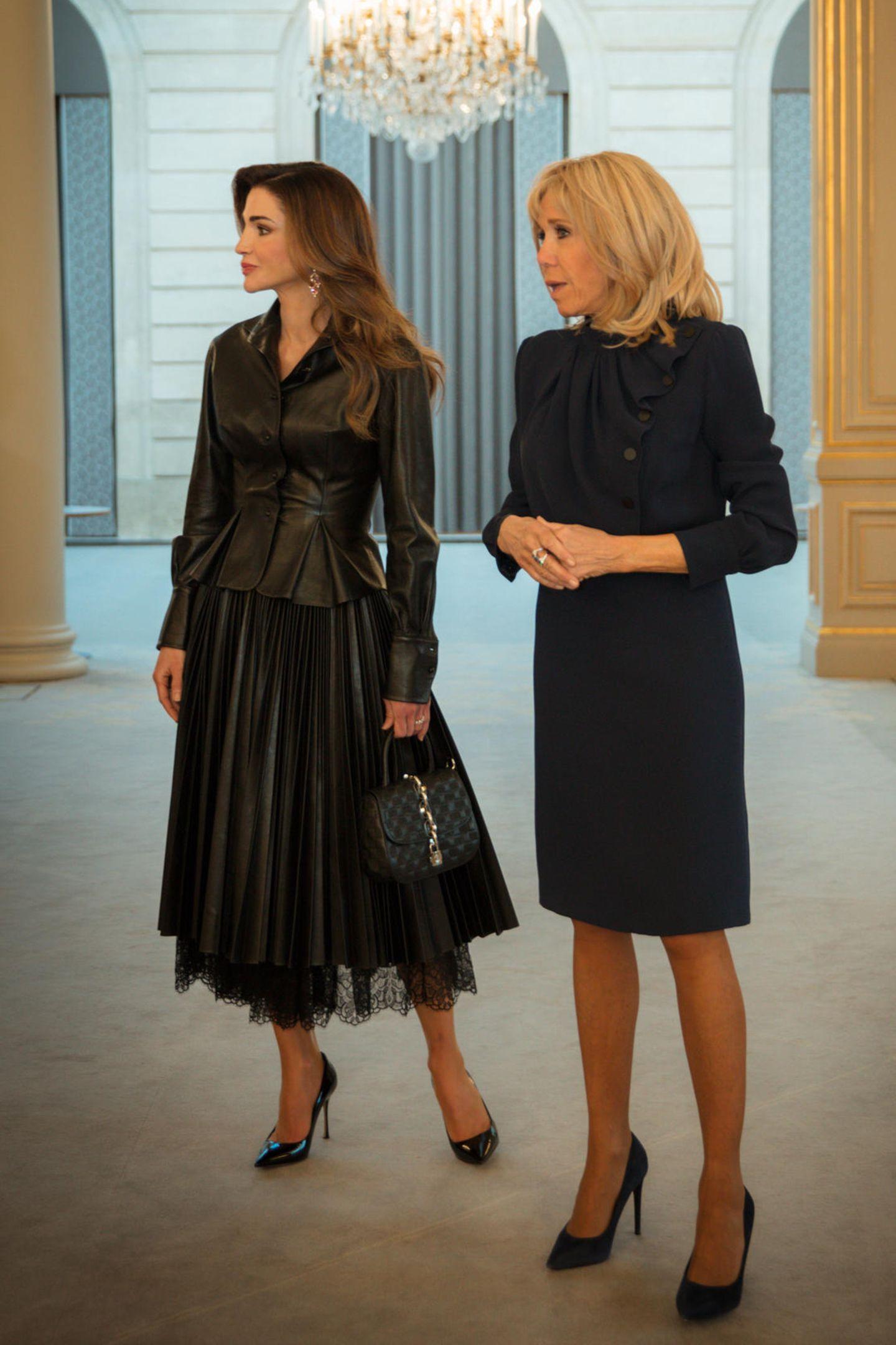 Zwei Fashionistas im Dienste der internationalen Politik: BeimStaatsbesuch des Königspaares von Jordanien hat sich Brigitte Macron für ein elegantes, knielanges Kleid mit Drapierung in Dunkelblau entschieden. Style-Star Königin Rania setzt derweil auf einen gewagten All-over-Lederlook.