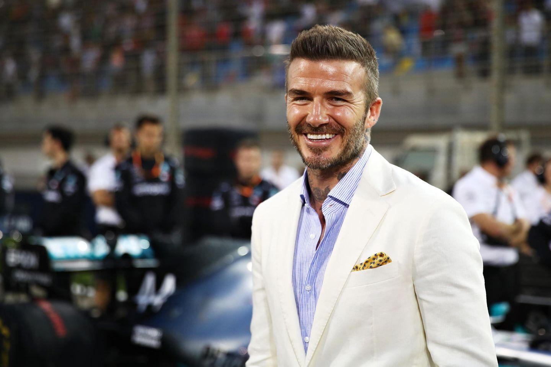 Der Ex-Fußballer David Beckham hat gute Laune: Er freut sich beim großen Rennen von Behrain für seinen Landsmann Lewis Hamilton.