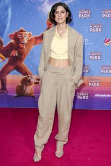 """Bei der Premiere von """"Willkommen im Wunder Park"""" verwandelt Lena Meyer-Landrut einen Anzug, der eher nach 80er-Jahre-Gebrauchtwagenhändler aussieht, in einen modernen Look. Ihr kurzes Poloshirt ist schließlich voll im Trend."""