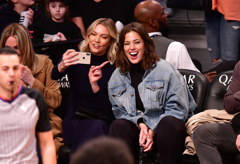 """Ganz nach dem Motto """"Girls just wanna have fun"""" albern die Topmodels Karlie Kloss und Ashley Graham auf den Zuschauerbänken eines Basketball-Spiels der Brooklyn Nets in New York City herum. Ein paar Erinnerungs-Schnappschüsse dürfen bei solch einer ausgelassenen Stimmung natürlich nicht fehlen."""