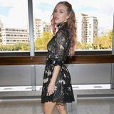 Zur Pariser Fashion Week reist sie in einem eleganten Kleid und hohen Stiefelletten.