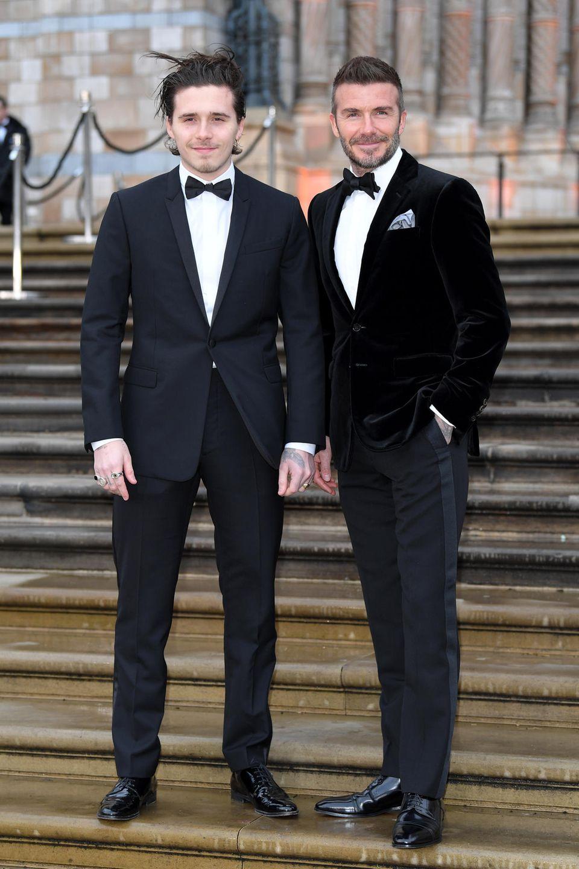 """5. April 2019  Zwei Männer, ein verschmitztes Lächeln: David Beckham und sein 20-jähriger Sohn Brooklyn erscheinen beide in einem schwarzen Anzug mit schwarzer Fliege zur Weltpremiere des Films """"Our Planet"""". Die Ähnlichkeit zwischen Vater und Sohn ist unverkennbar."""
