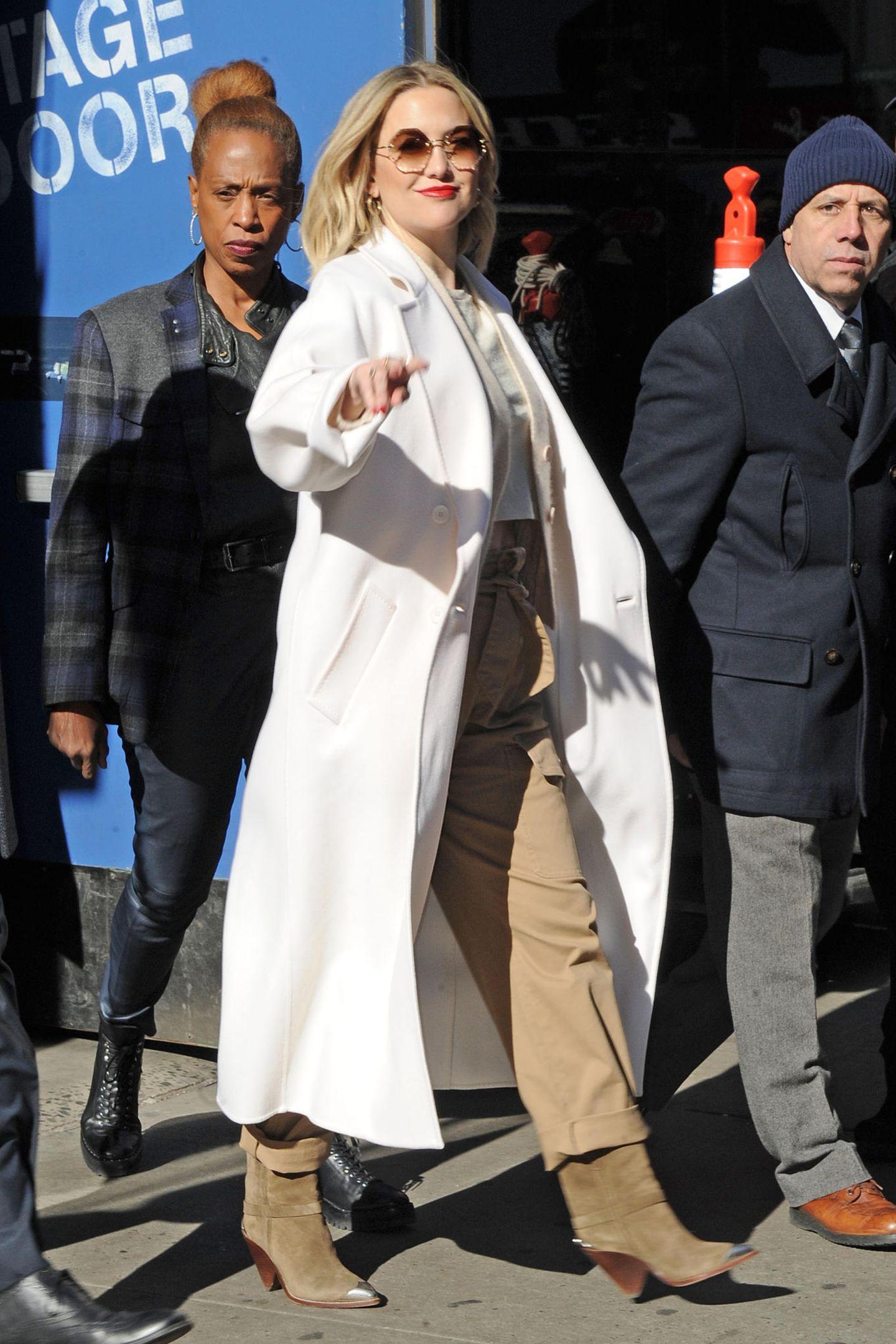 Kate Hudson ist bester Laune und wählt passend dazu auch ein helles Outfit. Sie zeigt, wie schön Beige-und Weißtöne miteinander harmonieren. Der knallige Lippenstift bildet ein farbliches Highlight.