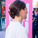 Auffällige Perlen-Stickereien am Oberarm und vergoldete Ohrringe in Form einer Feder verleihen dem Look das gewisse Etwas.
