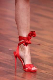 Auch untenrum geht es verspielt weiter: Victoria Swarovski trägt rote, hohe Sandaletten, die an ihrem Knöchel gebunden sind.