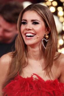 """Bei diesem Lächeln dürfte den Zuschauern von """"Let's Dance"""" das Herz aufgehen: Moderatorin Victoria Swarovski zeigt sich in Show Nummer drei in einem zauberhaften Look mit niedlichen Details. Zu einem roten Federkleid kombiniert sie auffällige, funkelnde Herz-Ohrringe. Doch nicht nur ihre Accessoires überzeugen ..."""
